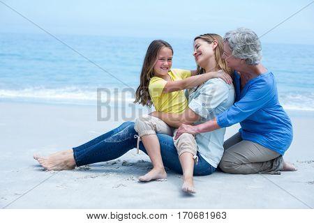 Happy multi-generation family resting at sea shore