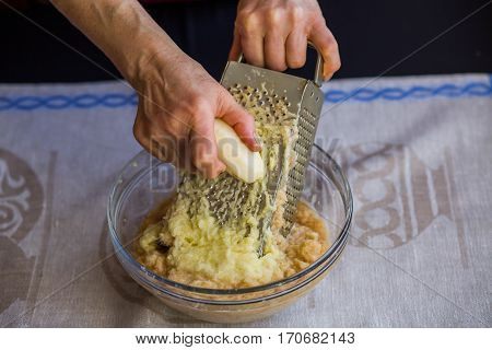 Raw Potatoes Shredded On A Grater. Arms. National Russian Dish. Potato Pancakes.