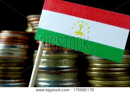 Tajikistan Flag Waving With Stack Of Money Coins Macro
