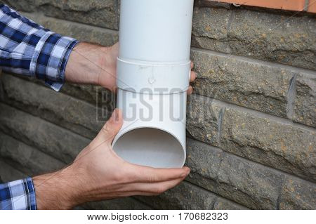 Man installing plastic rain gutter system pipeline. Guttering Gutters Plastic Guttering Guttering & Drainage by Handyman hands. Guttering Down pipe Fittings. DIY.