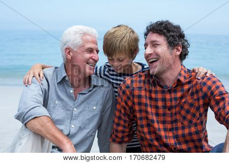 Close-up of cheerful multi-generation family relaxing at beach