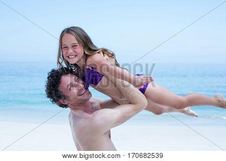 Portrait of cheerful shirtless man lifting daughter at sea shore