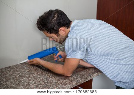 Side view of man using pest control injection while standing at home