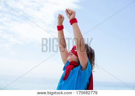 Close-up of boy in superhero costume pretending to fly at beach