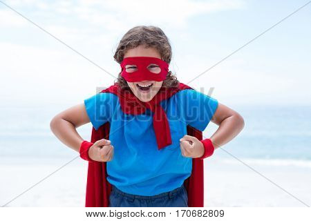 Portrait of cheerful boy in superhero costume flexing muscles at sea shore