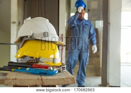 Yellow and White Helmet with Working Tool of Engineer Craftsman on Workbench at Construction site with Background of Male in working uniform as Technician Engineering or Civil work Concept poster