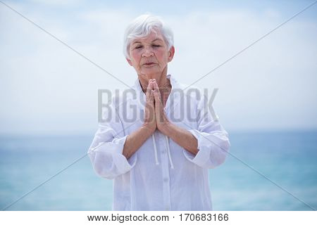 Senior woman with hands clasped at beach against sky