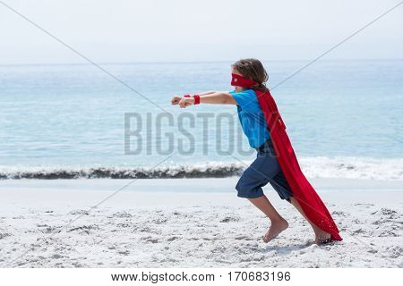 Full length of boy in superhero costume running with clenched fist at sea shore