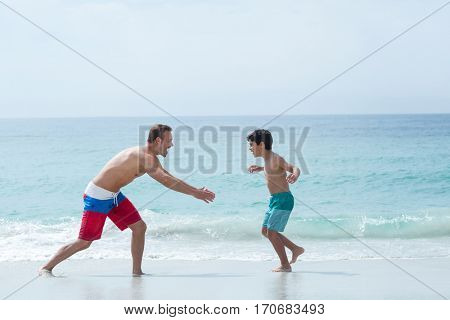 Father chasing son on sea shore at beach