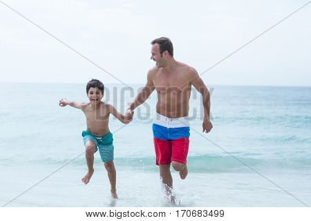 Father and son holding hands while running on sea shore at beach