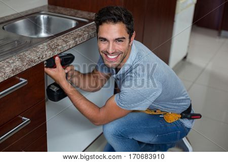 Portrait of cheerful man using cordless hand drill at home