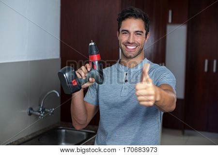 Portrait of happy man showing thumbs up while holding cordless hand drill at home