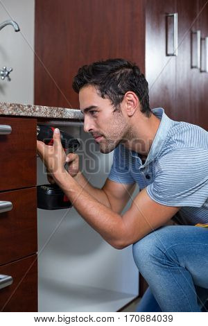 Man using cordless hand drill while crouching at home