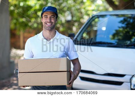 Portrait of smiling delivery man holding cardboard box while standing by van