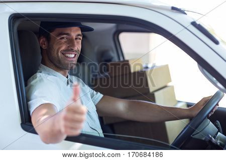 Portrait of smiling delivery man showing thumbs up while driving van