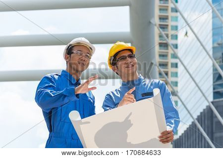 Two Engineer or Architect discuss on Modern Building Project at Construction site in Urban City