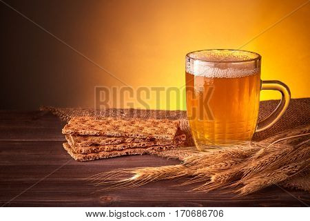 Still life of glass mug with light beer, wheat ears and crispbread  on a wooden table on a yellow background with copy space.