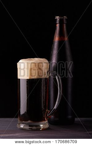 Cold bottle of beer with drops of water and fresh foamy beer in a glass mug are standing on wooden table on a black background.