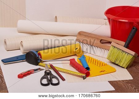 Still life from rolls of wall-paper and various tools for wallpapering. Repair. Home renovation.