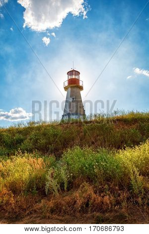 Lighthouse on background blue sky with cloud and green grass bright summery day landscape