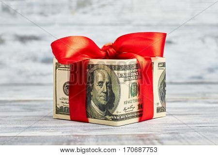 Dollars wrapped by red bow. Money is best present.