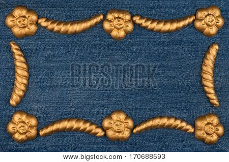 Luxury frame made of gold stucco plaster lying on denim. With space for your text