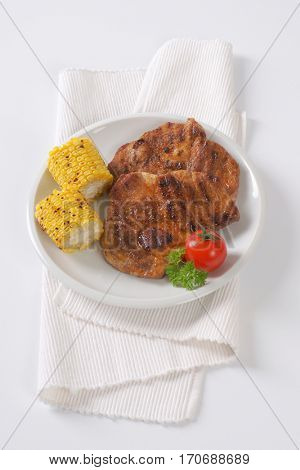 slices of grilled pork meat and corn cob on white plate