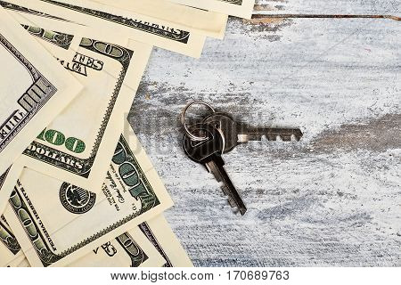 Keys and dollars on wood. Fulfill your dream.