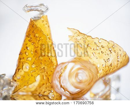 Pieces of cannabis oil concentrate aka shatter rolled on a cone and isolated against white background
