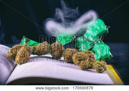 Detail of dried cannabis buds (Green Crack God strain) arranged over opened bible with smoke - medical marijuana concept background
