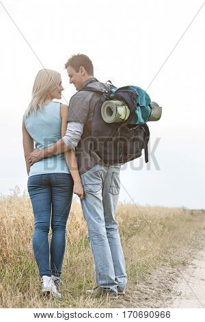Rear view of romantic hiking couple looking at each other while standing at field