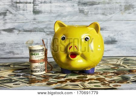 Piggy bank, dollars and coins on wooden surface. Capital for purchase.