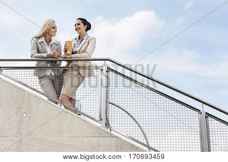 Low angle view of happy businesswomen discussing while standing by railing against sky