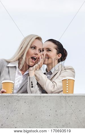 Low angle view of happy businesswomen with disposable coffee cups sharing secrets while standing on terrace against sky