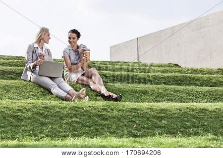 Full length of young businesswomen with disposable coffee cup and laptop sitting on grass steps against sky