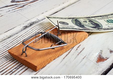 Mousetrap and banknote on wood. Risky financial business.