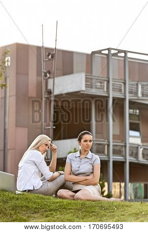 Displeased young businesswomen sitting on office lawn