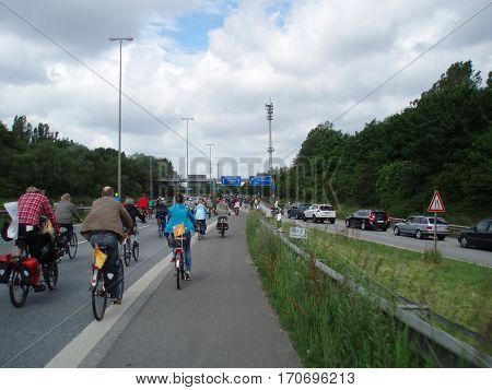 Hamburg, Germany - June 17, 2012: A large crowd of bicycle riders on a Autobahn, a german highway. It is temporarily closed for cars and the car drivers on the right have to wait until all cyclists have passed. Demonstration for development of ecological