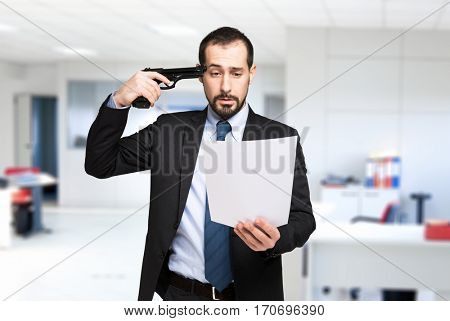 Businessman pointing a gun to his head while reading a document