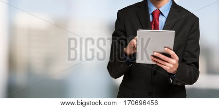 Detail of a businessman using his tablet. Large bright copyspace