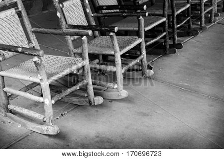 Many wooden rocking chairs on cement porch