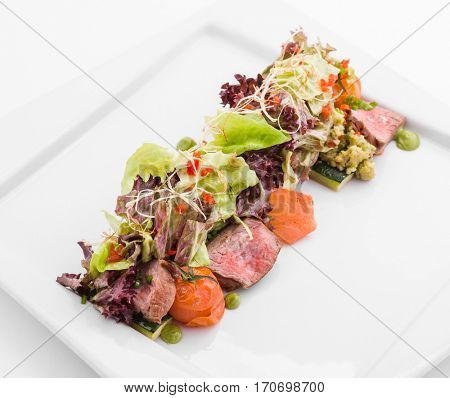Delicious cold meat with tomatoes and greens on plate