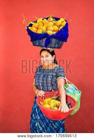 ANTIGUA, GUATEMALA - DEC 23, 2015; Unknown young Guatemalan woman carries fruit in a baskets at her head and hands on Dec 23, 2015, Antigua, Guatemala.