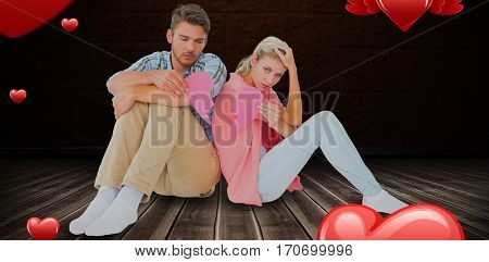 Attractive young couple sitting holding two halves of broken heart against floorboard against brown wall 3D