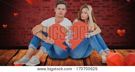 Young couple sitting on floor with broken heart shape paper against light on red brick wall