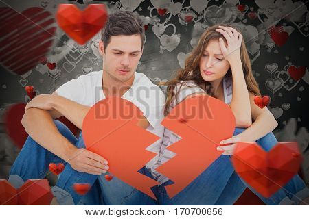 Young couple sitting on floor with broken heart shape paper against love heart pattern