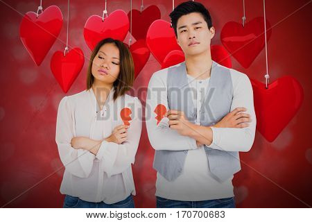 Young couple holding broken heart against valentines heart design 3d