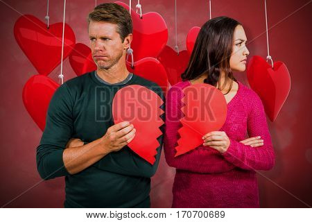 Serious couple holding cracked heart shape against valentines heart design 3D