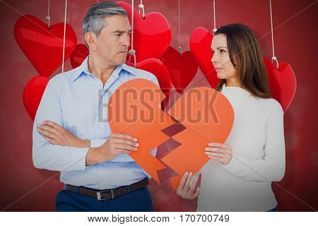 Couple holding broken heart shape paper against valentines heart design 3d