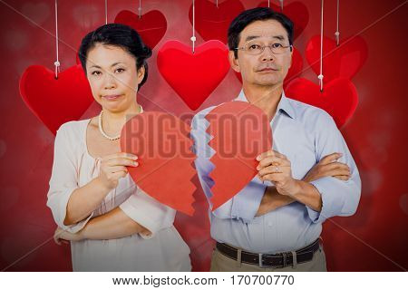 Couple holding broken heart against valentines heart design 3d
